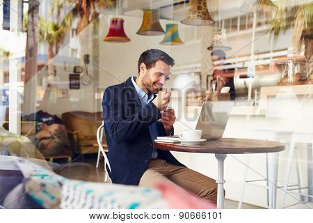 Young man sitting in a cafe eating a dessert