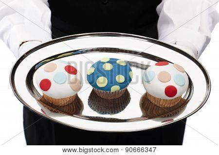 Waiter holding cupcakes