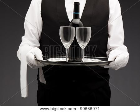 Waiter with wine and two glasses