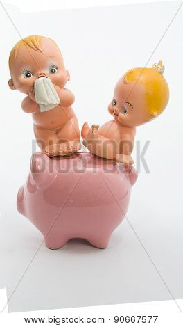 babys sitting on the floor with a piggy bank