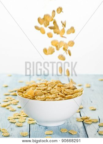 Cornflakes falling into the white bowl.  Morning breakfast.
