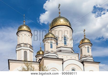Golden Domes Of Russian Orthodox Church With Cross Against Blue Sky