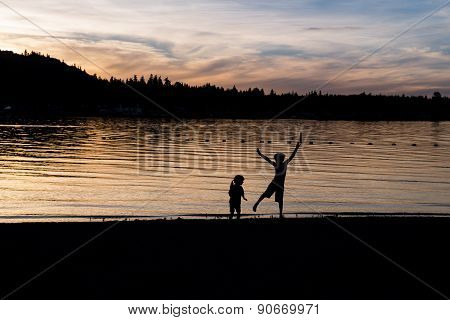 Silhouette Of Kids Dancing On The Beach In Twilight