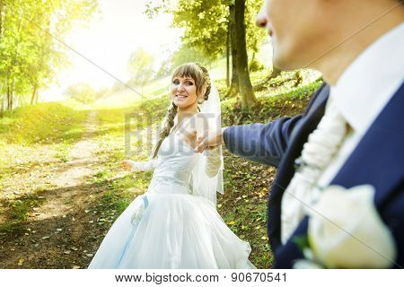 The bride is leading groom on a road