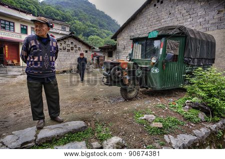 Chinese Peasants In Village Street, Next To Three-wheeled Green Car.