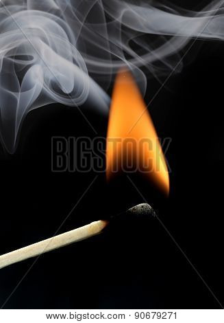 Burning matchstick, orange flame and gray smoke on black background