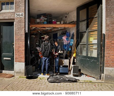 Young musicians are rehearsing in the garage.