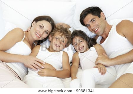 Overhead View Of Young Family Lying In Bed