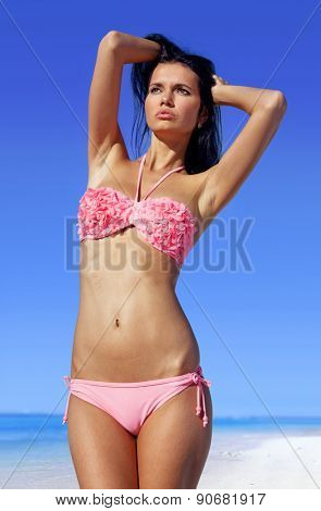 attractive woman sunbathing in pink bathing suit on beach