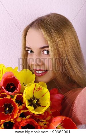 Portrait of young woman with beautiful bouquet of tulips on wallpaper background