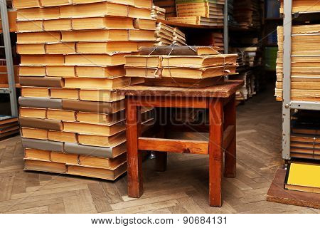 Many books on wooden chair in library