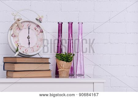 Interior design with alarm clock, plant, decorative vases and stack of books on tabletop on white brick wall background