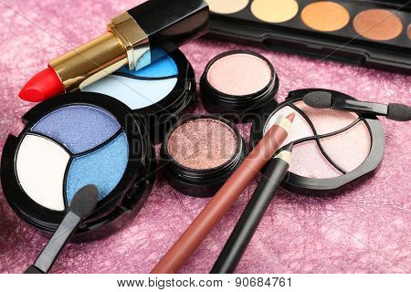 Set of colorful cosmetics on pink textured background