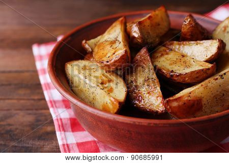 Baked potatoes in bowl on table close up