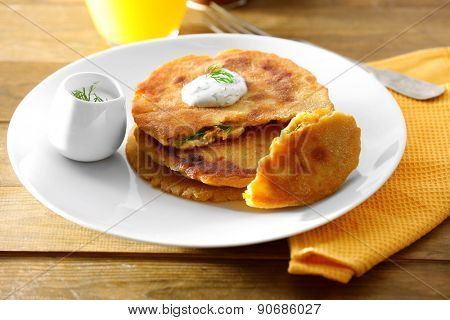 Stack of corn tortillas with stuffing and glass of juice on wooden table background