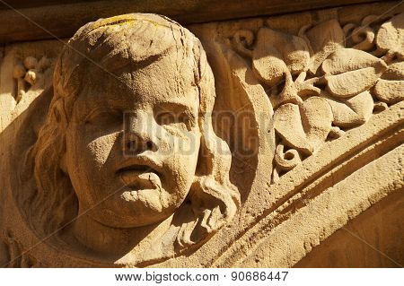 A lovingly designed head of a child of weathered sandstone