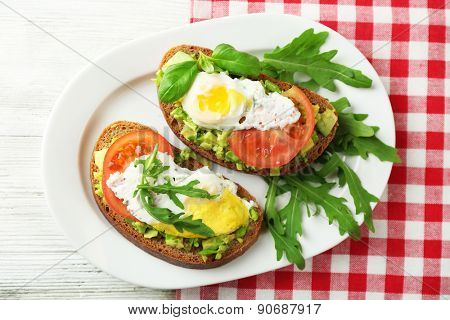 Tasty sandwiches with egg, avocado and vegetables on plate, on wooden background