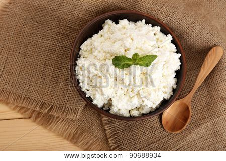 Cottage cheese in bowl on sackcloth background