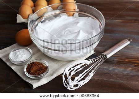 Whipped egg whites for cream and other ingredients on wooden table, closeup