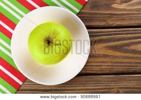 Apple on saucer with napkin on wooden table, top view