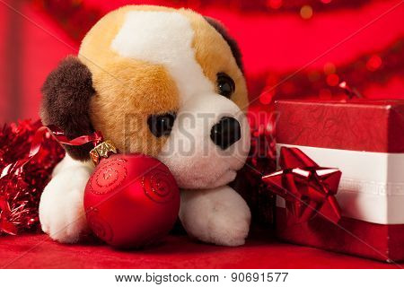 Toy dog plush puppy with christmas ornaments over red