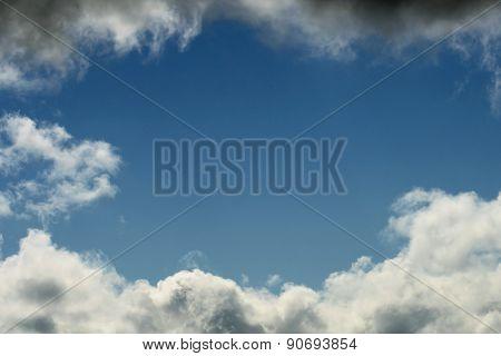 White fluffy clouds framing a bright blue sky