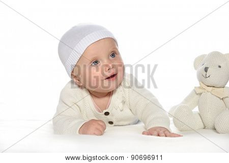 baby girl child lying down on white blanket smiling happy white  hat warm cloting fashion portrait face studio shot isolated on white caucasian teddy bear