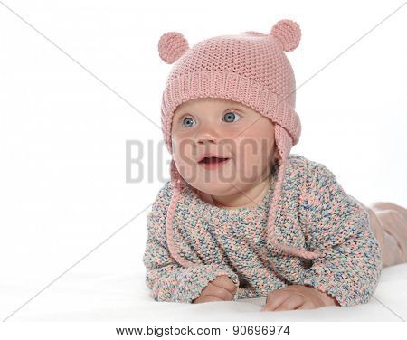 baby girl child lying down on white blanket smiling happy pink fashion portrait face studio shot isolated on white caucasian  hat warm cloting