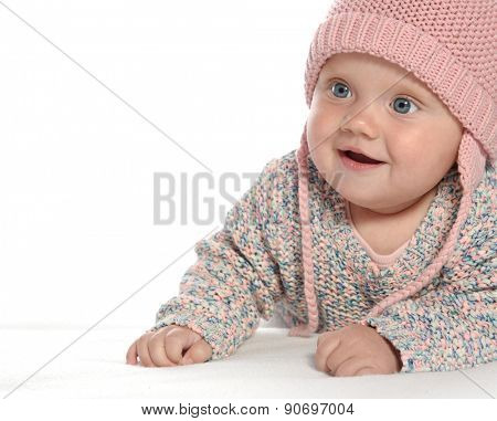 baby girl child lying down on white blanket smiling happy pink warm hat fashion portrait face studio shot isolated on white caucasian