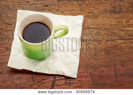 green stoneware cup of espresso coffee on a napkin against rustic wood with a copy space