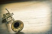 stock photo of forlorn  - Old rusty trumpet lays on wooden floor in the morning light - JPG