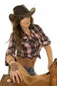 pic of cowgirl  - a cowgirl leaning on her saddle with her tattoo on her hand - JPG