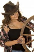 picture of cowgirls  - A cowgirl with her hand on a wagon wheel with her tattoo on her hand and chest showing - JPG
