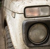 pic of monster-truck  - Muddy white vehicle covered in dried mud and headlamp - JPG