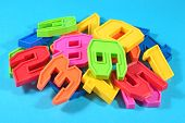 foto of blue things  - Heap of plastic colored numbers on a blue background close up - JPG