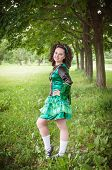 foto of cross-dress  - Young beautiful girl in irish dance dress and wig posing outdoor - JPG