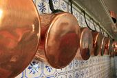 stock photo of saucepan  - Alignment of saucepans in a kitchen wall - JPG