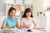 stock photo of preteens  - Smiling preteen Asian schoolgirls studying in classroom - JPG