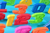 pic of blue things  - Colorful plastic numbers 123 close up on a blue background - JPG