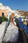 foto of runaway  - Runaway bride in a wedding dress in Santorini in Greece  - JPG