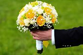 foto of fiance  - Fiance holding a bright wedding bouquet of white and yellow roses outdoor on green natural background horizontal picture - JPG