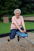 picture of senior-citizen  - senior citizen woman on a playground seesaw - JPG