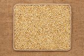 foto of sackcloth  - Frame made of rope with barley grains on sackcloth as background texture - JPG