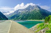 pic of dam  - Dam and azure mountain lake  on the background of the high peaks of the Alps - JPG