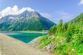 foto of dam  - Dam and azure mountain lake  on the background of the high peaks of the Alps - JPG