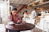 image of internet-cafe  - Young woman using laptop in a cafe - JPG