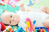 picture of playmate  - little baby on the carpet with toys - JPG