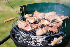 stock photo of grils  - Pork Meat Chop Cooked On The Barbecue Gril Outdoor - JPG