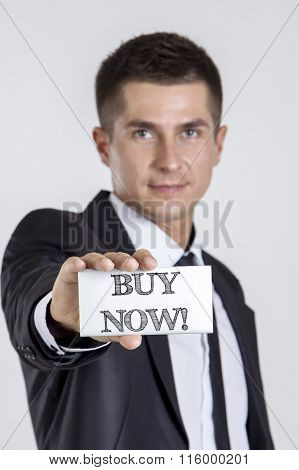 Buy Now! - Young Businessman Holding A White Card With Text