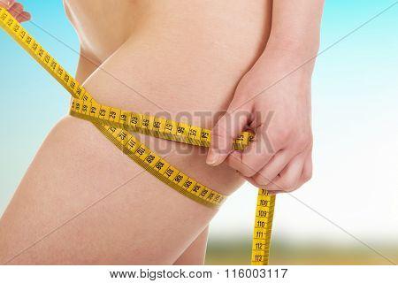 Slim woman measuring her thigh.